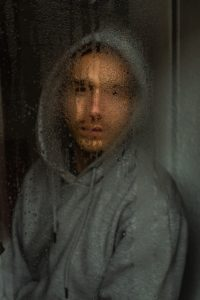 Man staring out of rainy window