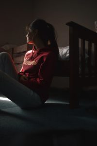 Young woman sitting on floor leaning against bed
