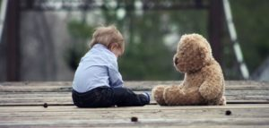 Little boy sitting with his teddy