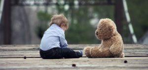 Little boy sitting with his teddy
