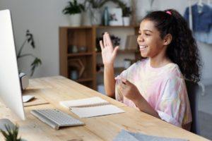 Young girl waving at computer screen