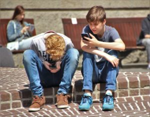 two young teenage boys sat on curb
