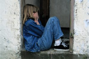 Young girl crying in doorway